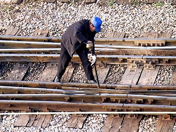 This rail worker faces many dangers every day. If you have been injured while working for a railroad company, call a Garland FELA attorney now.